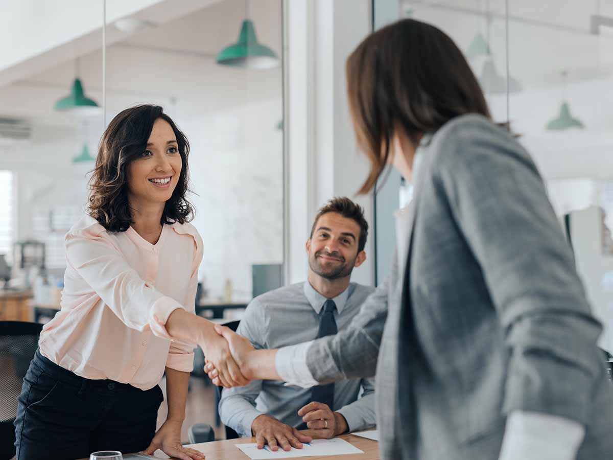 Woman transitioning from contract to employee with handshake